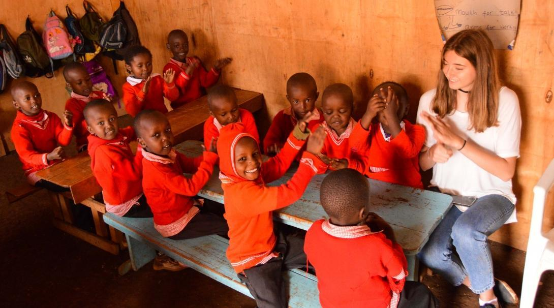 Female Projects Abroad volunteer working with children in Kenya sits with kindergarten children in a classroom during an educational activity.